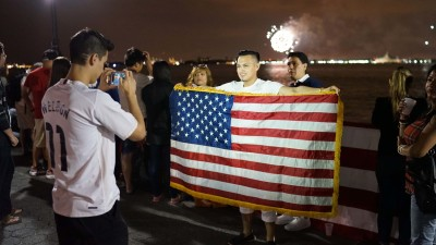 Immigrant with American flag July 4 2015